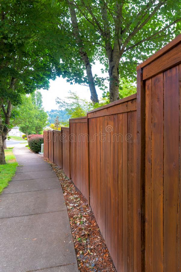 Wooden Fence along residential Neighborhood Sidewalk. Wooden Fence along suburban residential neighborhood concrete sidewalk royalty free stock photos