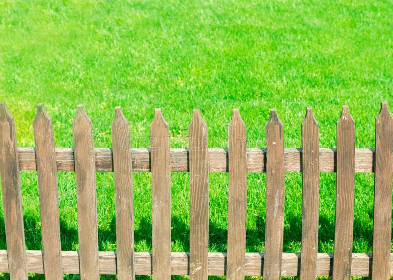 Wooden fence on a background of green grass. Outdoor nature stock photography