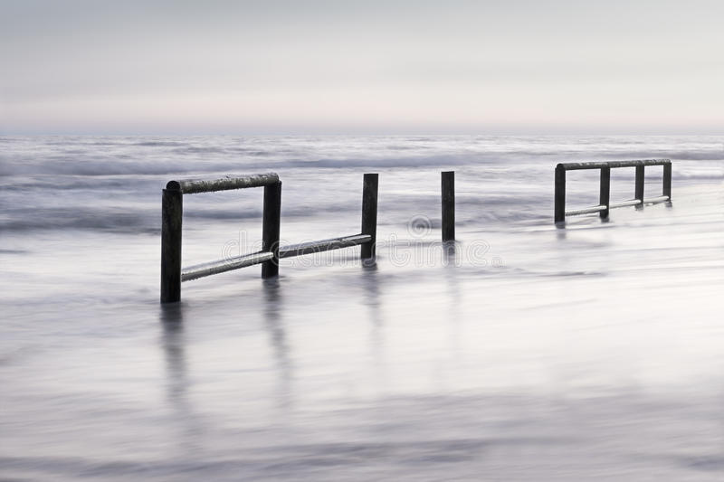 Wooden fence in sea water at sunset stock photos