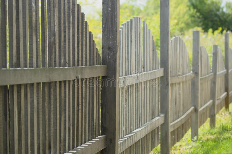 Wooden fence made in the form of arches. Stretching into the distance stock photography