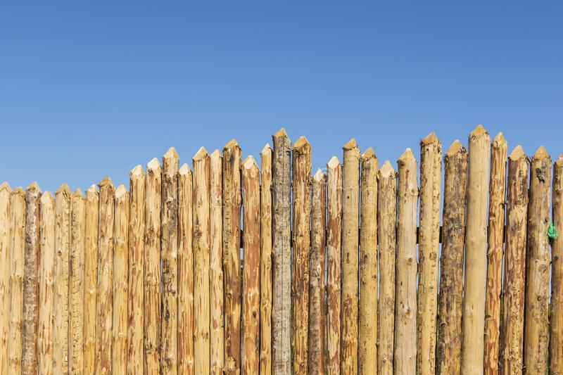 Wooden fence made of sharpened planed logs. royalty free stock photography