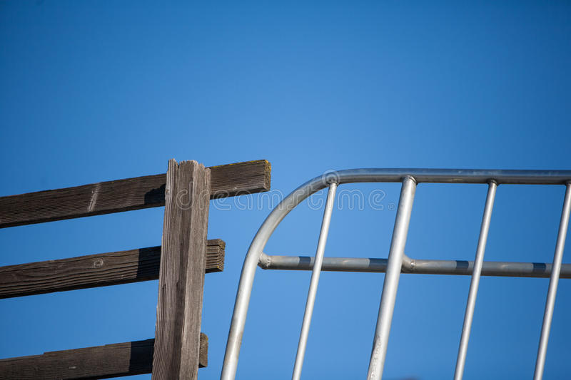 Wooden fence and metal gate juxtaposed against blue sky royalty free stock image