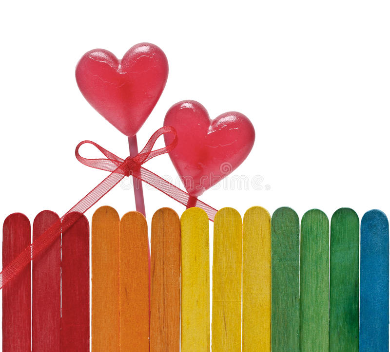Wooden fence in rainbow colors and two lollipops in heart shape stock photography