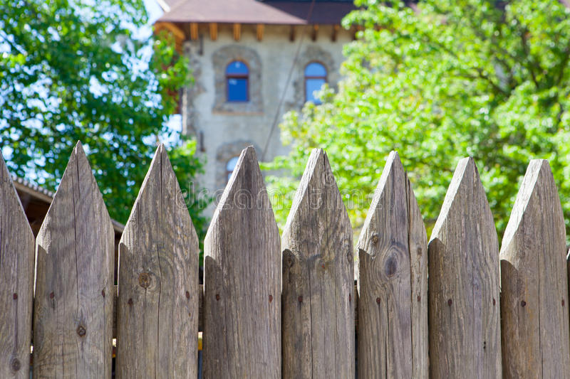 Wooden fence of sharpened logs stock images