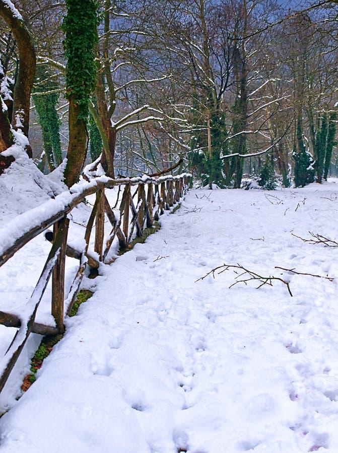 Wooden  fence on snow covered land, in Agios Nikolaos (Saint Nicholas) park, Naousa Greece royalty free stock photo