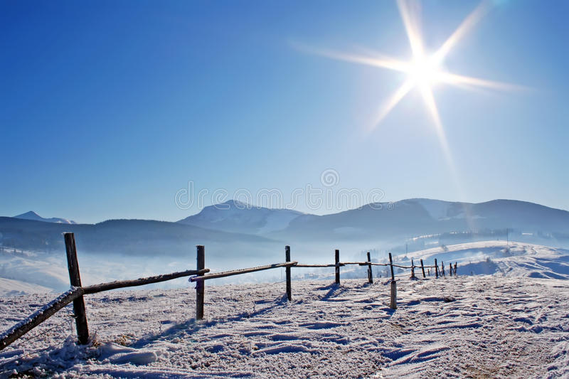 Wooden fence in snowcovered mountains. Under shiny sun royalty free stock image