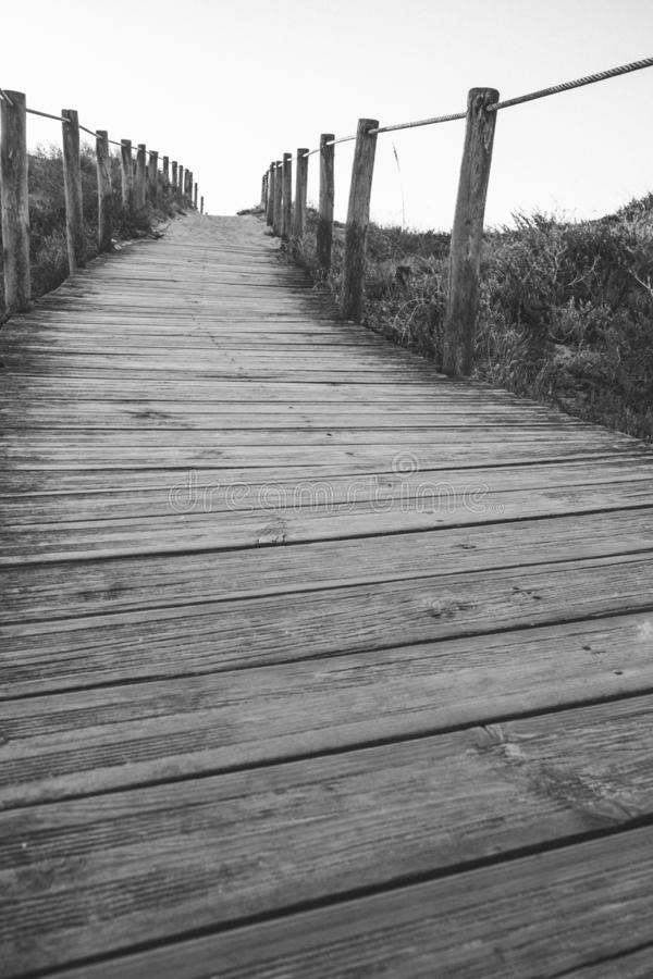 Wooden fence and walkway to beach black and white. Empty path monochrome. Walking concept. stock images