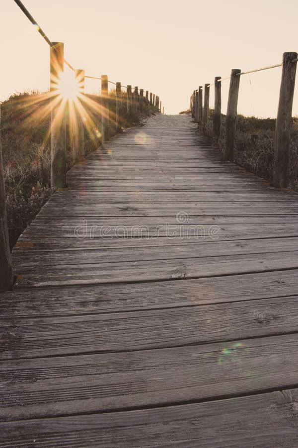 Wooden fence and walkway to beach faded. Empty path in sunlight. Walking concept. Camino de Santiago way. Wooden fence and walkway to beach faded. Scenic sunset royalty free stock photo