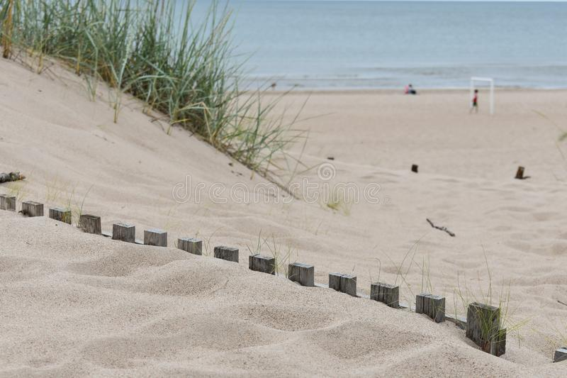 Wooden fences buried under the white sand stock image