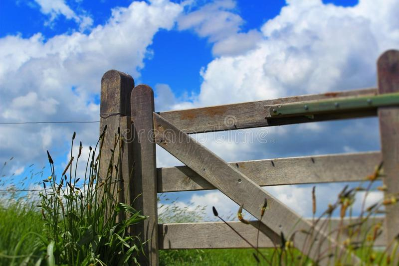 Wooden fench blue sky. Wooden fench field grass blue sky clouds barrier gate stock photography