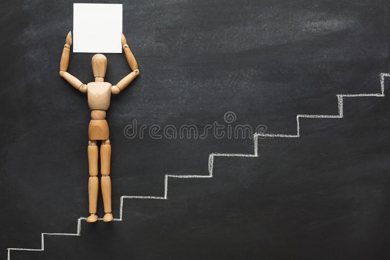 Wooden figure on drawn steps stock photo
