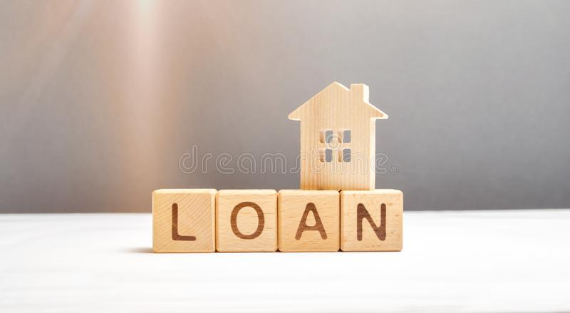 Wooden figure of the house and the cubes with the inscription loan. Mortgage programs and the purchase of affordable housing. For young families and citizens royalty free stock photography