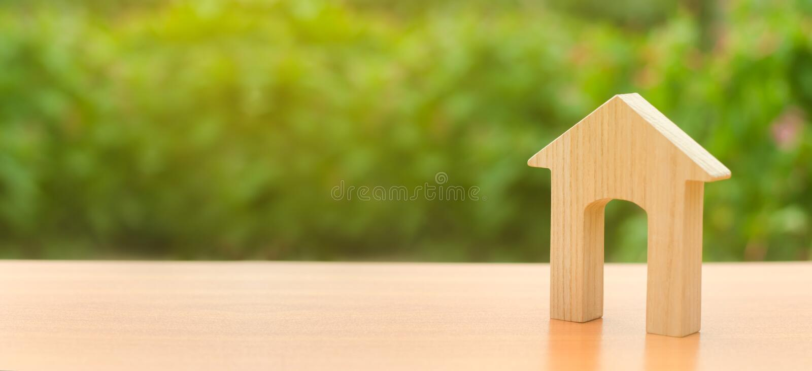 Wooden figure of a house with a large doorway on nature background. concept of buying and selling real estate, rent, investment. Home, Affordable housing royalty free stock image