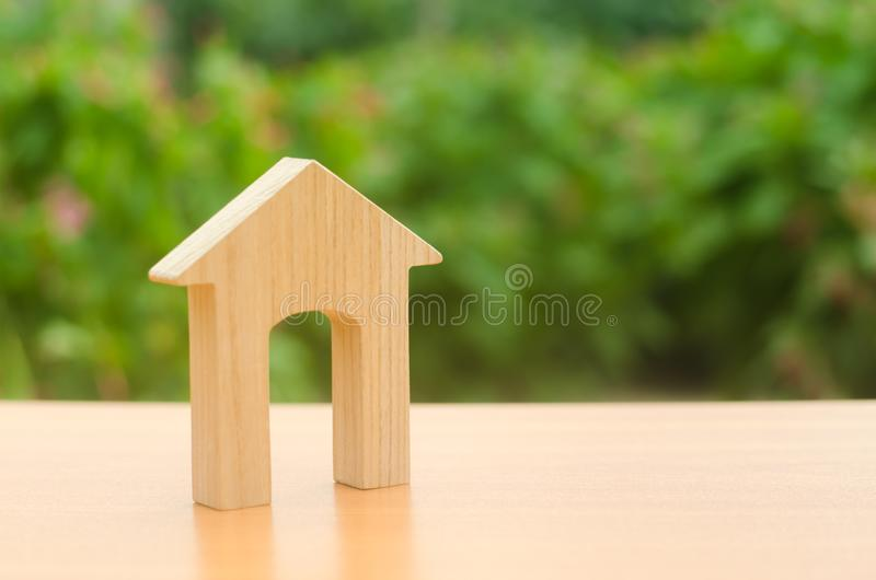 Wooden figure of a house with a large doorway on nature background. Home, Affordable housing, residential building. Concept of buying and selling real estate royalty free stock image