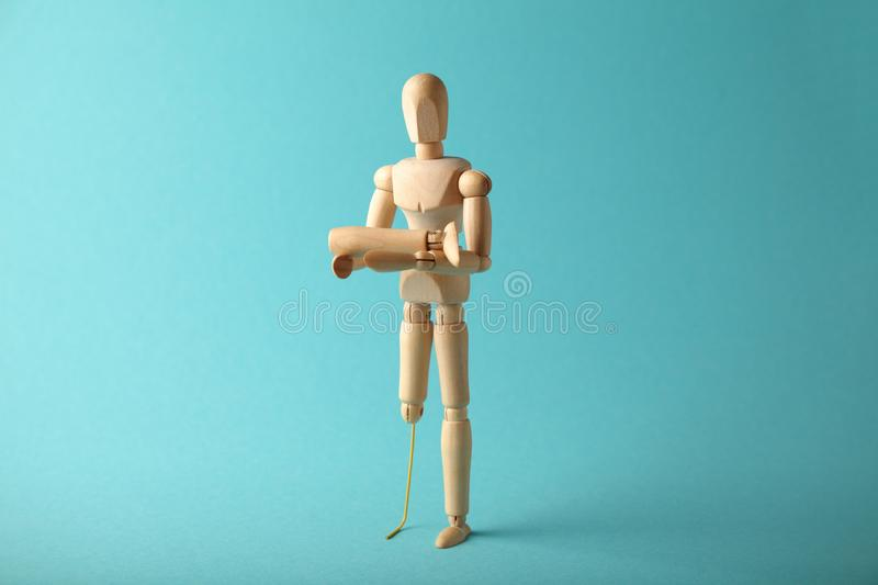 Wooden figure of man with artificial prosthetic leg. Amputee and disability concept royalty free stock photography
