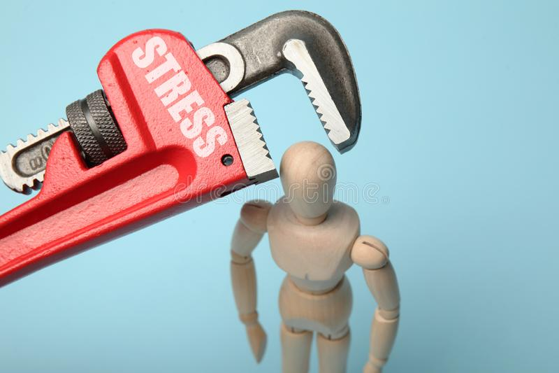 Wooden figure of man with clamped head in vice. Headache, stress, migraine stock photo