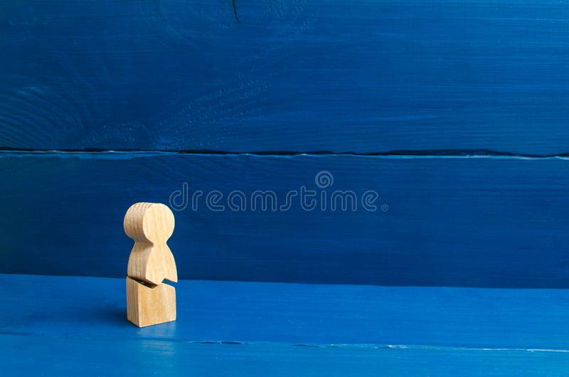 A wooden figure of a man with a crack. The concept of psychological stress and pressure. Could not stand our nerves and our health. Threat of life. Injury and stock photo