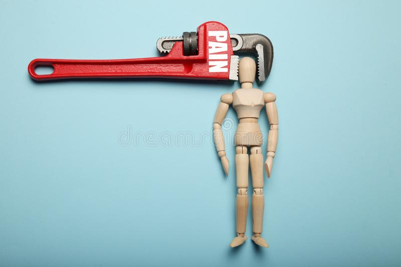 Wooden figure of man with his head clamped in vice with inscription Pain. Headache, stress, migraine stock images