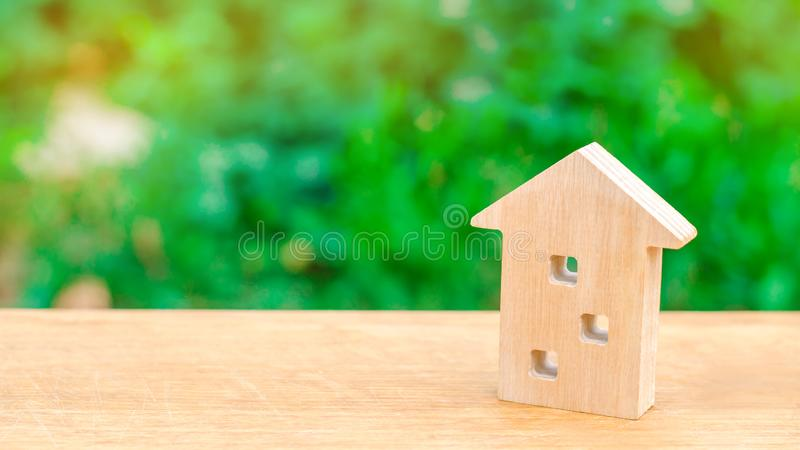 Wooden figure of a multi-storey house on a green background. Three-story house. Buying and selling of real estate, construction. A stock photography