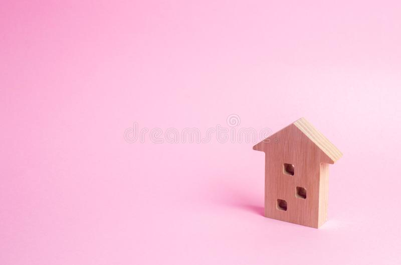 Wooden figure of a multi-storey house on a pink background. Three-story house. Buying and selling of real estate, construction. Ap royalty free stock photos