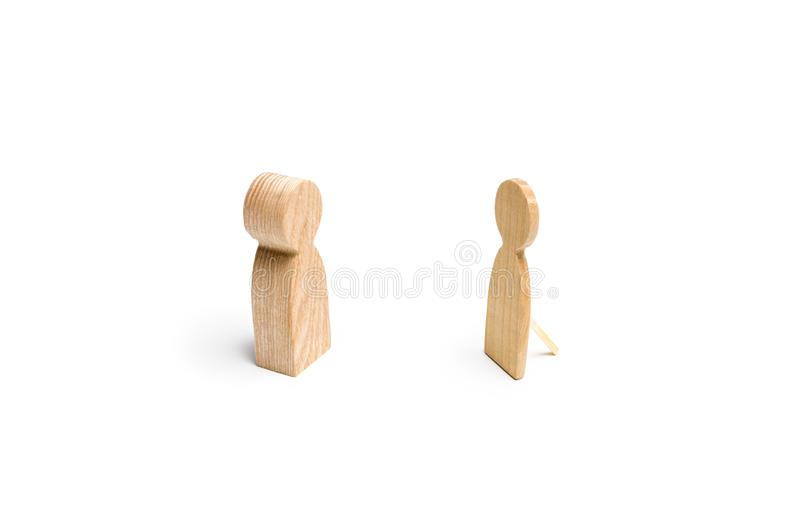 A wooden figure of a person is trying to communicate with a false figure of a person. The concept of deception, indifference. And emptiness, meaningless royalty free stock image