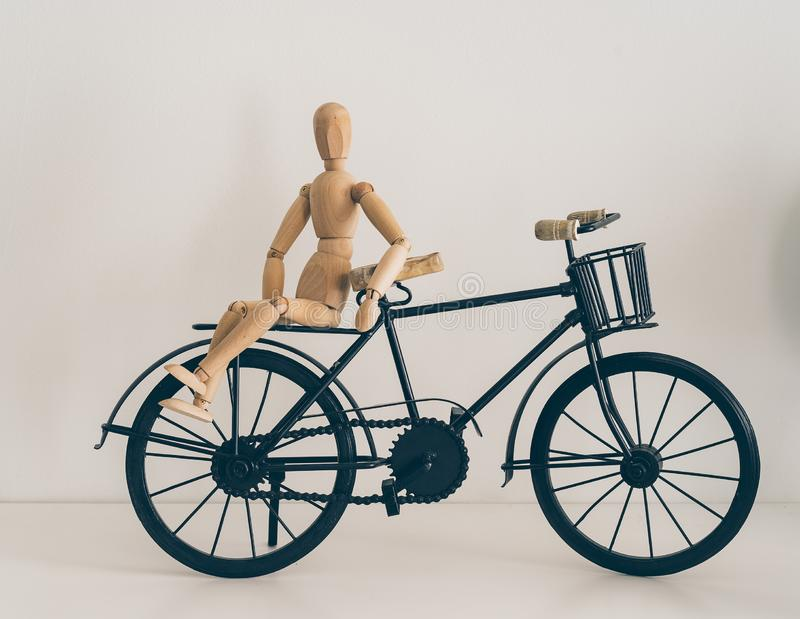 Wooden figure posing in a bicycle, travel and lifestyle.  stock image
