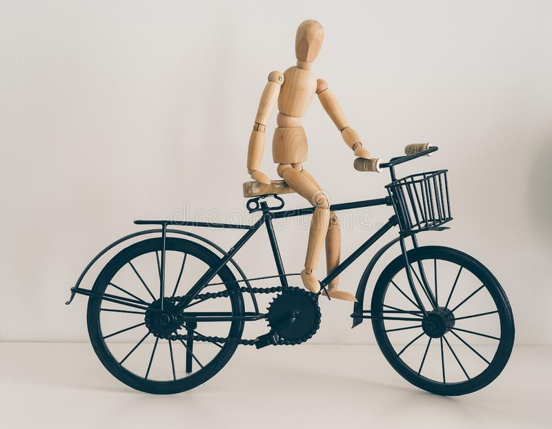 Wooden figure posing in a bicycle, travel and lifestyle.  royalty free stock photo