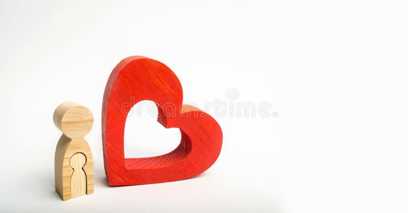 A wooden figure of a pregnant woman and heart. the future mother loves her baby. expectation and birth of a child. the last months royalty free stock image