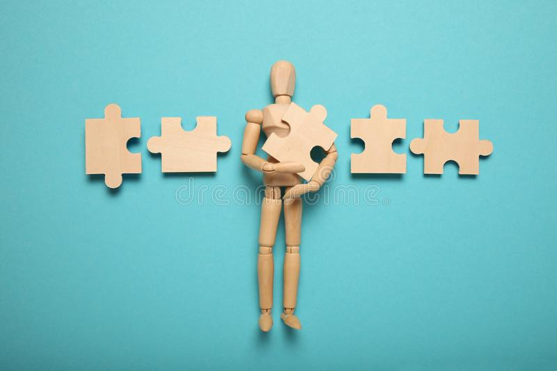 Wooden figure and puzzles, problem solving in business, new challenges. Innovation and teamwork royalty free stock photo