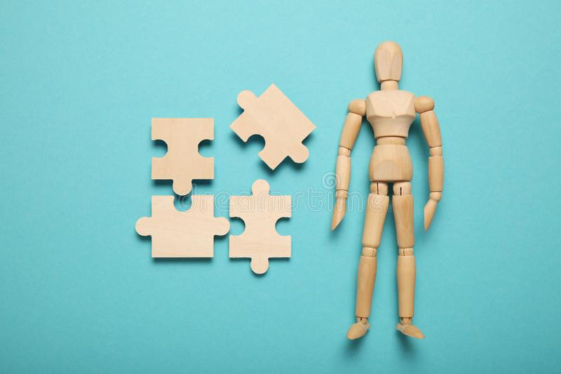 Wooden figure and puzzles, problem solving in business, new challenges. Innovation and teamwork.  royalty free stock photos