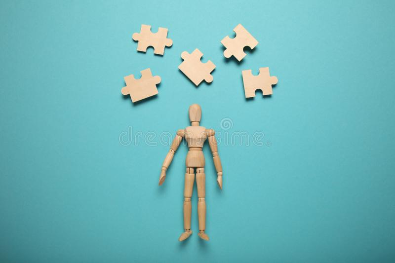 Wooden figure and puzzles, problem solving in business, new challenges. Innovation and teamwork.  stock photo