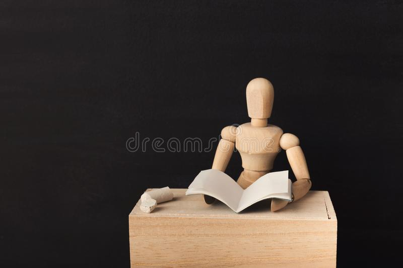 Wooden figure is reading a book against black background royalty free stock image