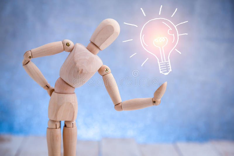 Wooden figure showing light bulb symbol stock image