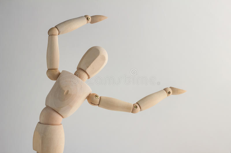 Wooden figure showing up blank space on white background. Copy space for your text stock photography