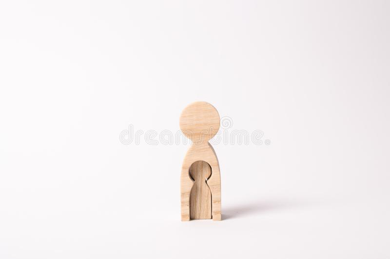 A wooden figure of a woman with a void inside in the shape of a child. The concept of the loss of child, abortion of pregnancy stock photos