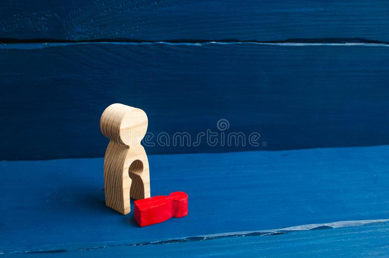 A wooden figure of a woman with a void from which a red child fell. The concept of the loss of a child, abortion of pregnancy, mis royalty free stock photography