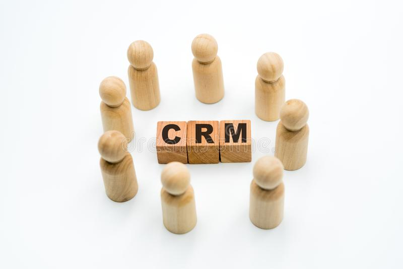 Wooden figures as business team in circle around acronym CRM Customer Relationship Management stock photography