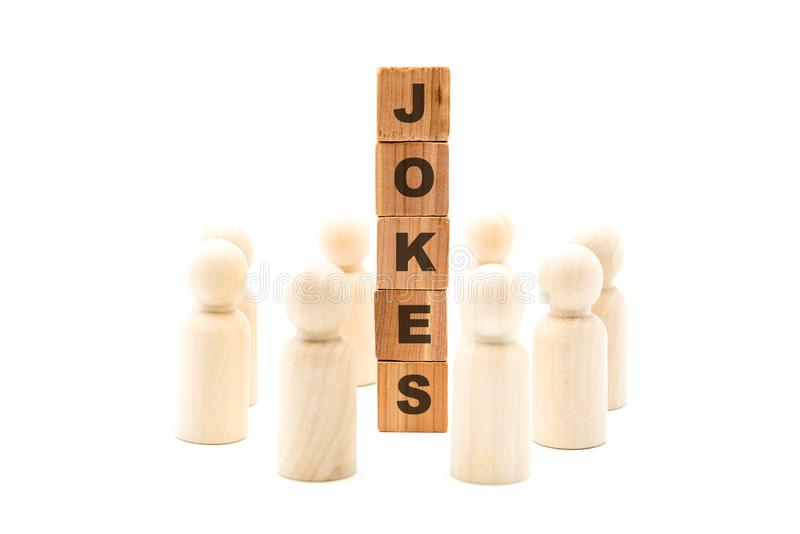 Wooden figures as business team in circle around word JOKES. Isolated on white background, minimalist concept stock images