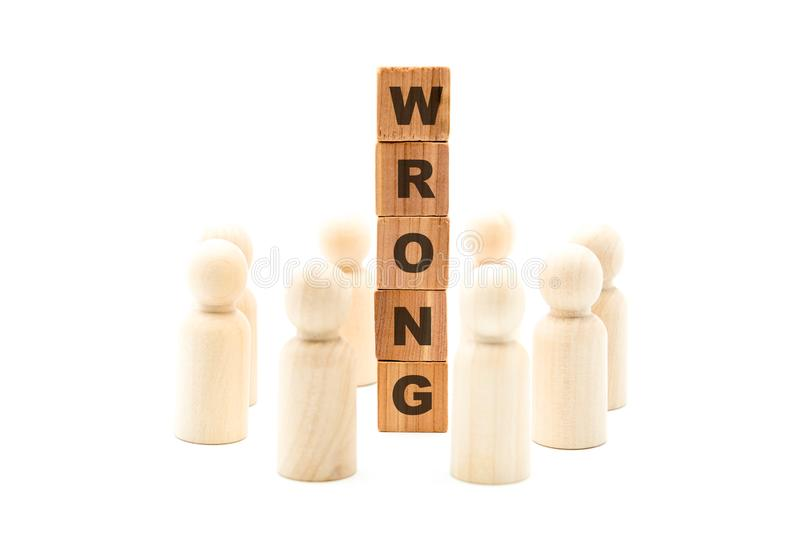 Wooden figures as business team in circle around word WRONG stock photo