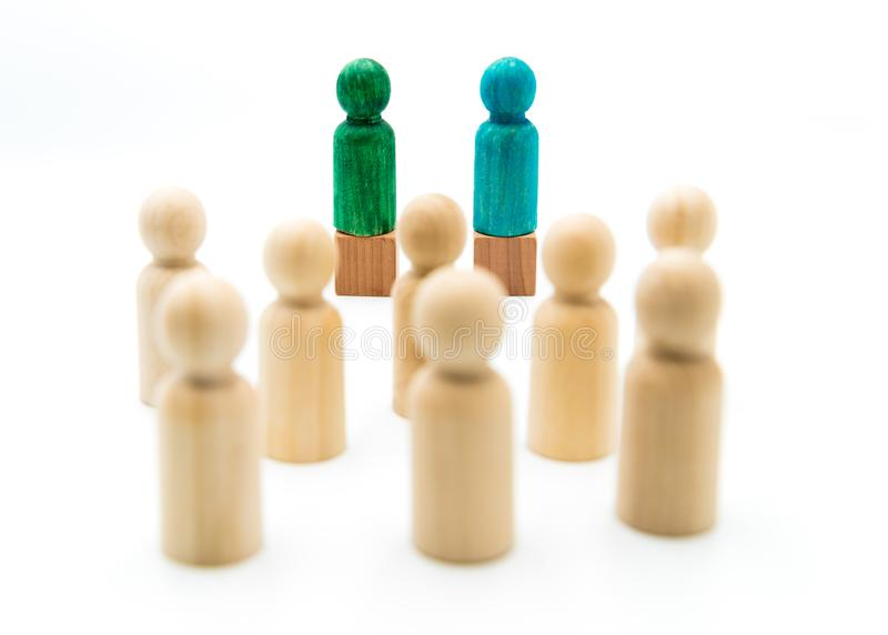 Wooden figures as a group listening to blue and green figures giving speech or debating. On white background royalty free stock photography