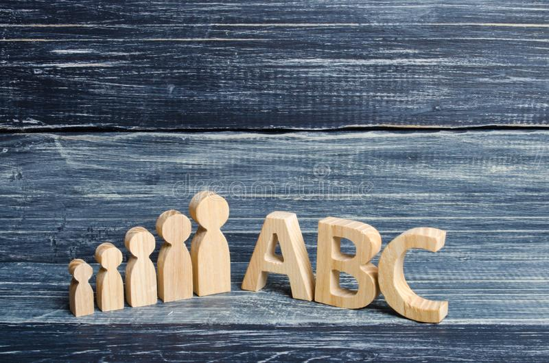 Wooden figures of children stand in a row from small to large near the letters of the English alphabet abc. The concept of educati stock image
