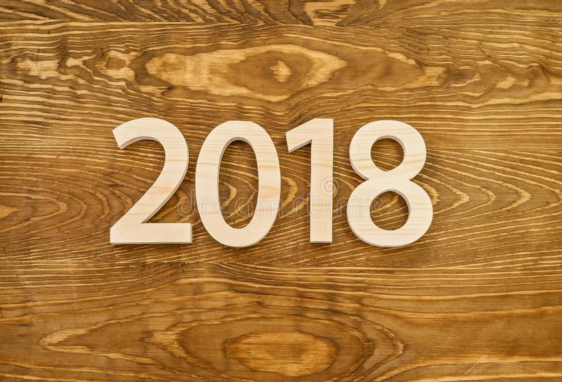 Wooden figures forming 2018, carved from light wood on the background of old wood. New Year Idea, postcard, poster, greetings. Fe royalty free stock photo