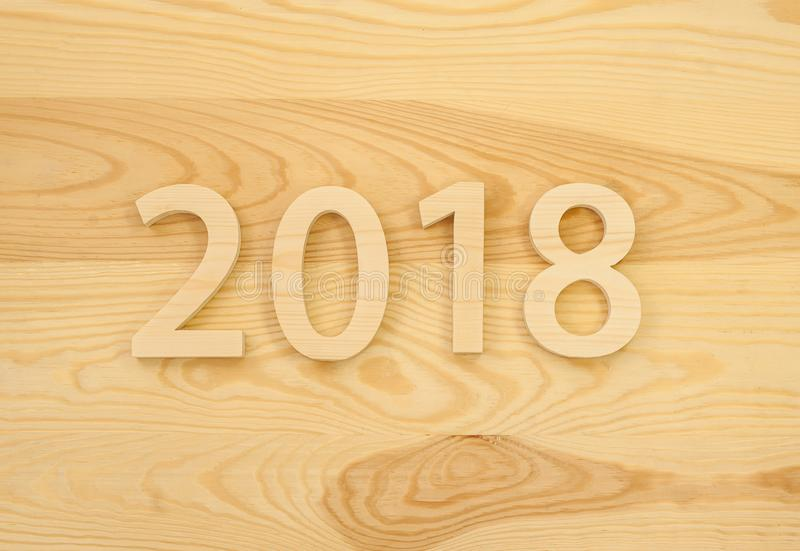 Wooden figures forming 2018, carved from light wood on the background of old wood. New Year Idea, postcard, poster, greetings. Fe stock photo