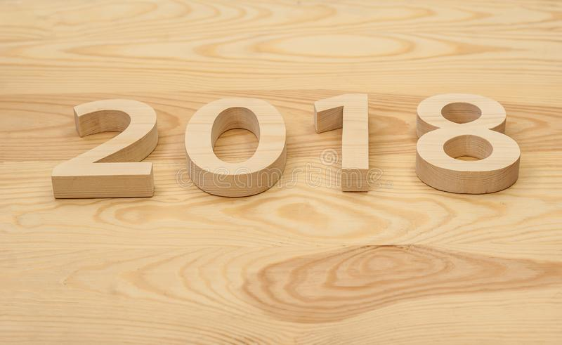 Wooden figures forming 2018, carved from light wood on the background of old wood. New Year Idea, postcard, poster, greetings. Fe royalty free stock images