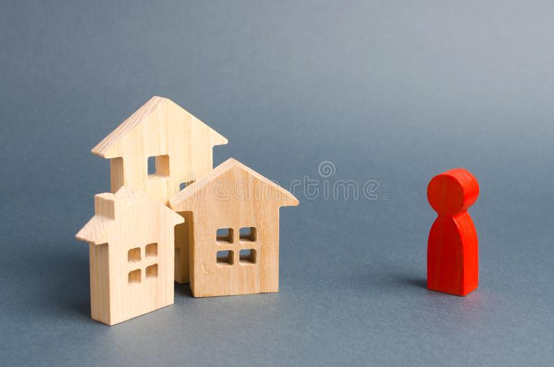 Wooden figures of houses and a red figure of the person on a gray background. Acquisition of real estate and assets. Increase liquidity and attractiveness of stock photos