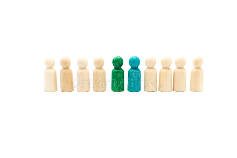 Wooden figures as a group listening to blue and green figures giving speech or debating. On white background royalty free stock image