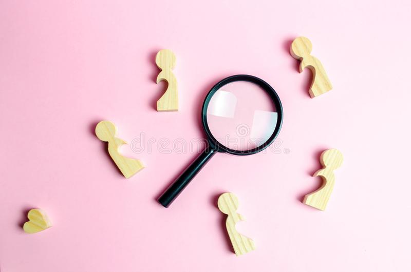 Wooden figures of lonely people around a magnifying glass. Search for love and creation of strong love relationships. Dating and flirt, search for a love royalty free stock photos