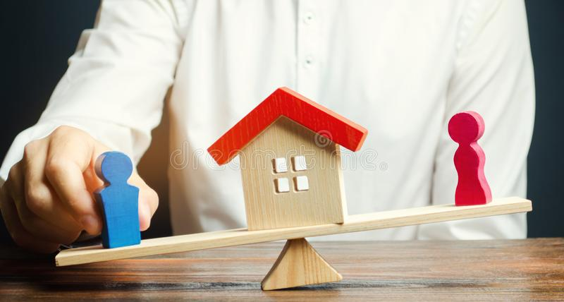 Wooden figures of a man and a woman on scales and a house between them. Division of property by legal means. Clarification of. Ownership of the housing. Divorce royalty free stock photo