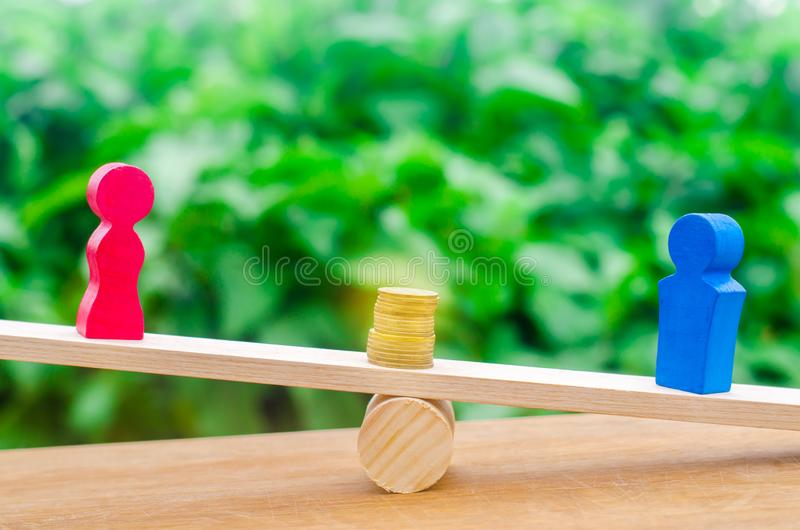 Wooden figures of a man and a woman stand on the scales and coins between them. concept of the gender pay gap. Income inequality. Balance royalty free stock photography