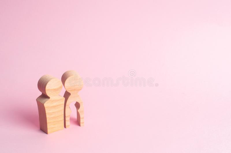 Wooden figures of a man and a woman with a void inside the body in the form of a child. Infertility in a couple. Loss of a single child. Medical problems. The royalty free stock photos